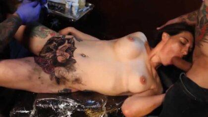 Marie Bossette chupando una polla mientras le hacen un tatuaje